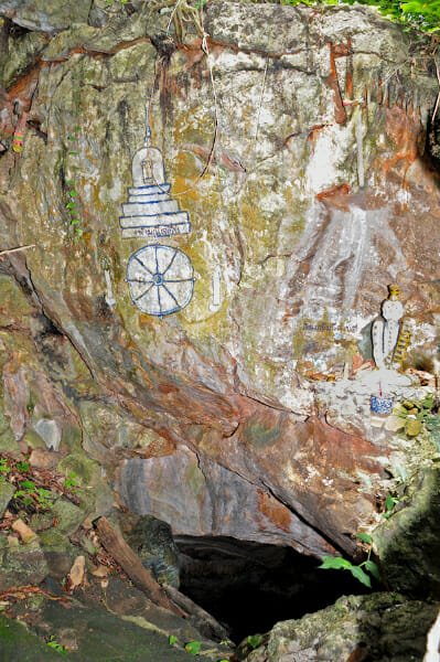 Buddhist drawings at the entrance to the cave