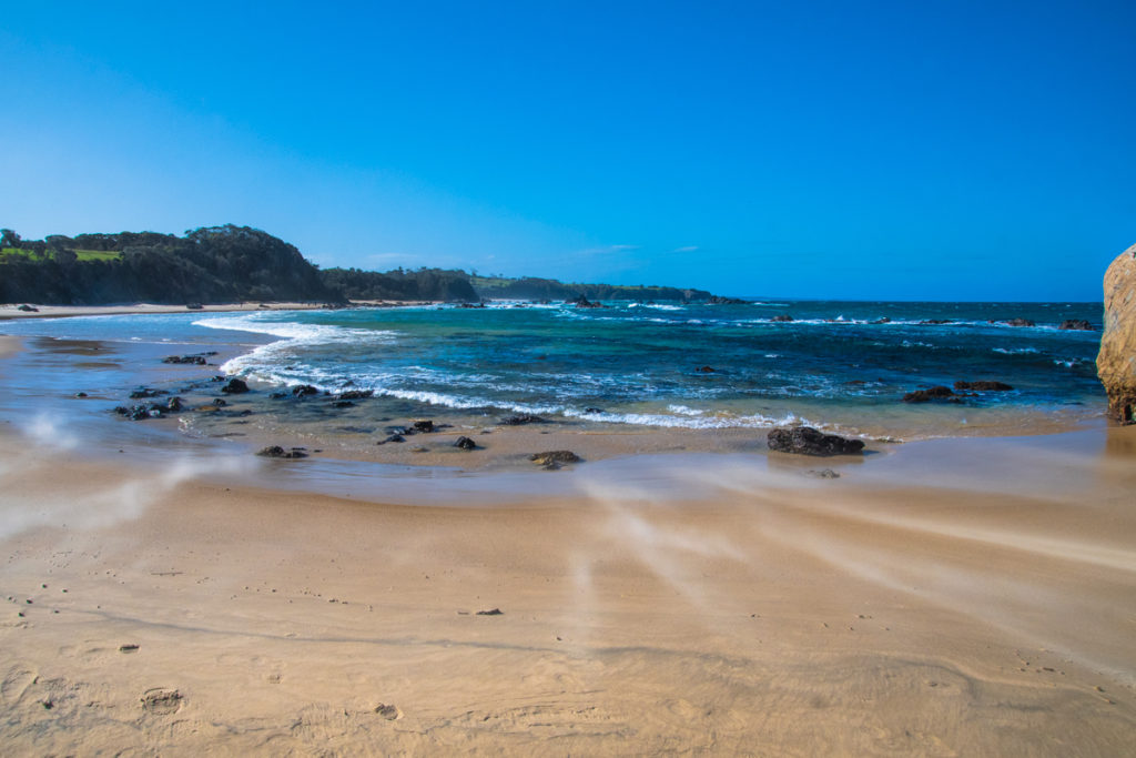 Strong wind blowing sand along Narooma surf beach